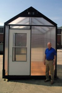 White man standing in front of temporary steel shelter