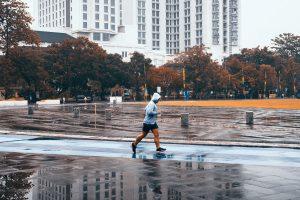 Guy running on wet street